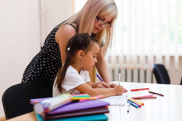 Junger vorschullehrer, der kleine mädchen im klassenzimmer unterrichtet