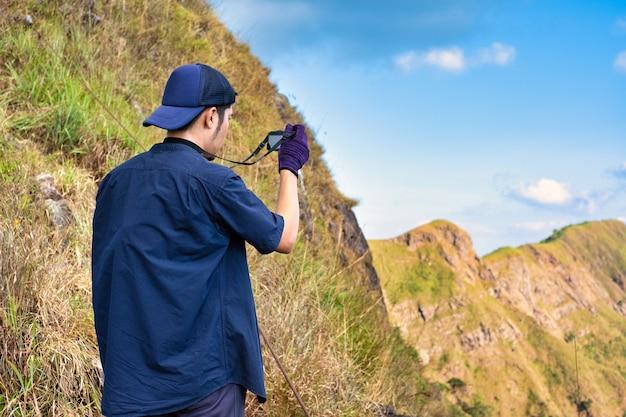 Junger wanderer, der eine fotografie entlang weg des terkkings macht. fotograf, der foto an der bergspitze macht.