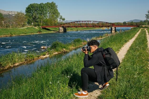 Junger wanderer, der foto von idyllischem fluss macht