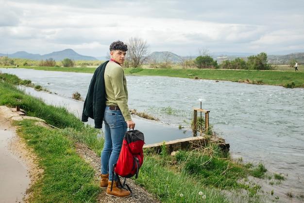 Junger wanderer, der nahe flüssigem fluss mit dem halten des rucksacks betrachtet kamera steht