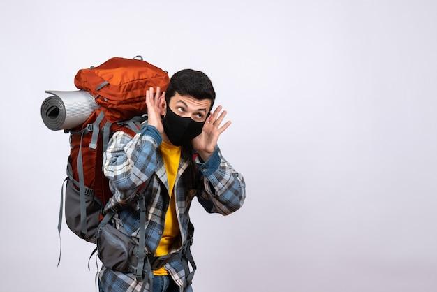 Junger wanderer der vorderansicht mit rucksack und maske, die auf etwas hören