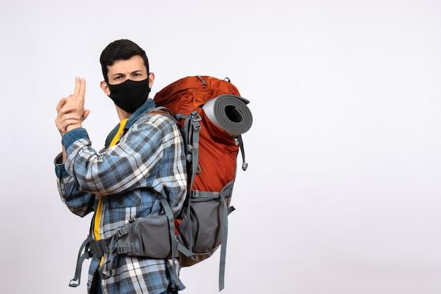 Junger wanderer der vorderansicht mit rucksack und maske, die fingerpistolenzeichen machen