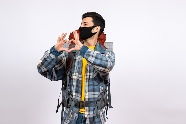 Junger wanderer der vorderansicht mit rucksack und maske, die herzzeichen machen