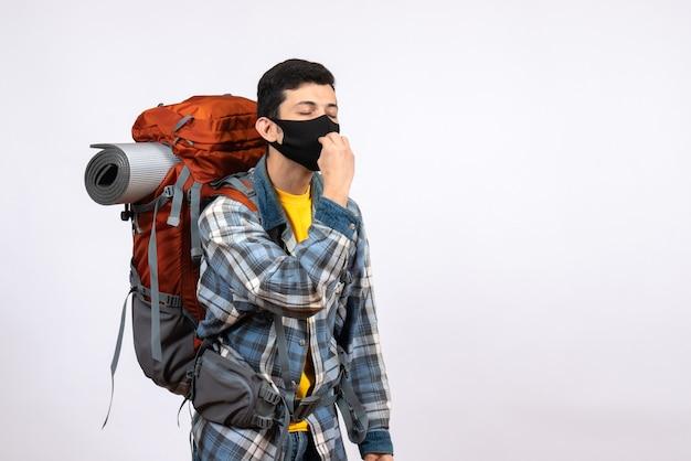 Junger wanderer der vorderansicht mit rucksack und maske, die leckeres zeichen machen