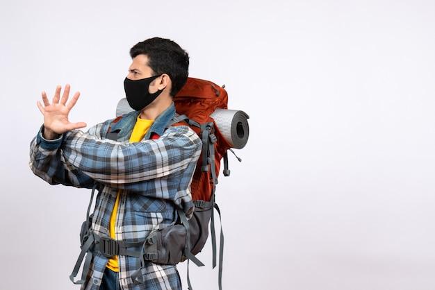 Junger wanderer der vorderansicht mit rucksack und maske, die versuchen, etwas zu stoppen