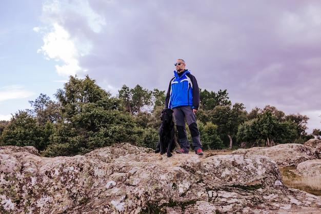Junger wanderermann am berg mit seinem schwarzen labrador auf einen felsen. bewölkter wintertag