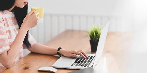 Junger website-manager, der heißen kaffee trinkt, während er auf computer-laptop tippt, der auf hölzernen arbeitstisch setzt. frauenentspannungszeitkonzept.