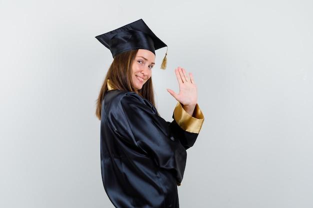 Junger weiblicher absolvent, der hand für begrüßung im akademischen kleid und in der fröhlichen vorderansicht winkend wendet.