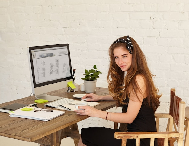 Junger weiblicher architekt, der beim arbeiten im büro schaut und lächelt. attraktive junge frau, die das neue bürogebäude studiert, das am schreibtisch im büro sitzt