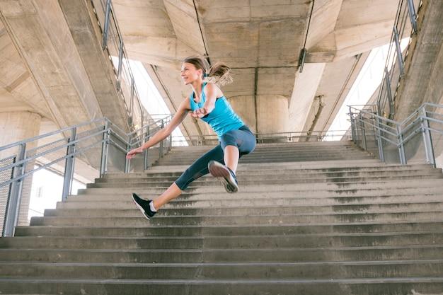 Junger weiblicher athlet in der sportkleidung, die über das konkrete treppenhaus springt