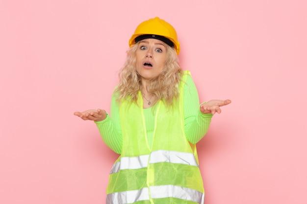 Junger weiblicher baumeister der vorderansicht im gelben helm des grünen bauanzugs, der auf dem rosa raumjobarchitektur-konstruktionsfoto aufwirft