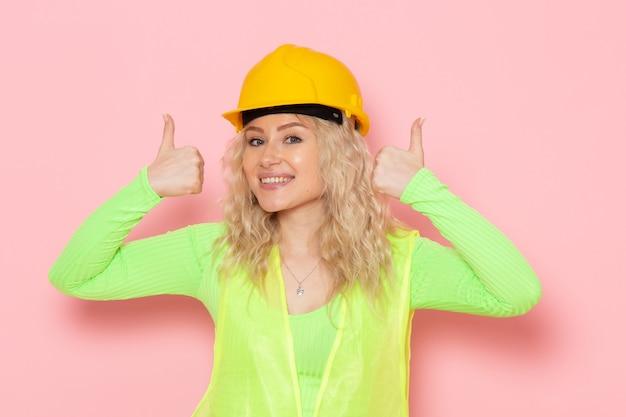 Junger weiblicher baumeister der vorderansicht im gelben helm des grünen bauanzugs, der gerade mit lächeln auf dem rosa raumarchitekturbaujob aufwirft