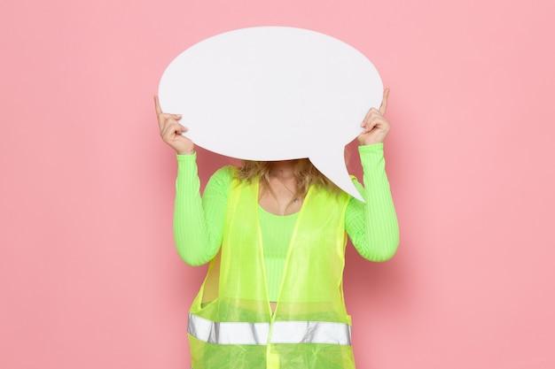 Junger weiblicher baumeister der vorderansicht im gelben helm des grünen bauanzugs, der weißes großes zeichen auf dem bauauftrag der rosa raumarchitektur hält