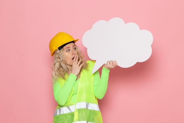 Junger weiblicher baumeister der vorderansicht im grünen bauanzughelm, der ein großes weißes zeichen auf dem rosa raumarchitekturbauarbeitsjob hält