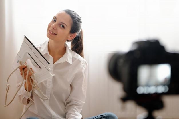 Junger weiblicher blogger mit kamera dslr vlogging rewievs haushaltsprodukt im modernen on-line-arbeitskonzept der flasche