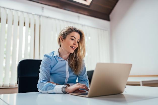 Junger weiblicher büroangestellter, der laptop verwendet.