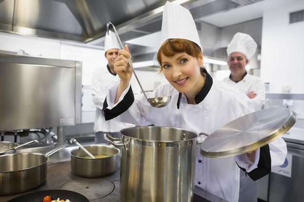 Junger weiblicher chef, der eine suppe schmeckt