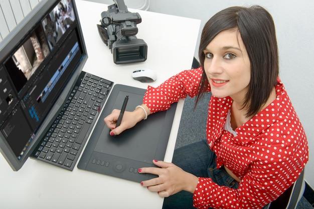 Junger weiblicher designer, der grafiktablett für die videobearbeitung verwendet