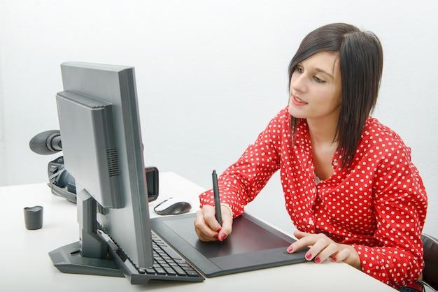 Junger weiblicher designer, der grafiktablette beim arbeiten mit computer verwendet