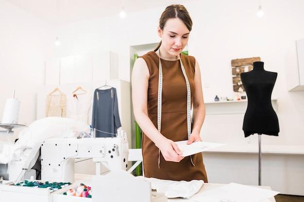 Junger weiblicher designer, der modeskizze im shop hält