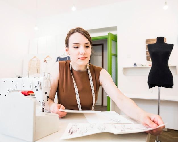 Junger weiblicher designer, der modeskizze über schreibtisch betrachtet