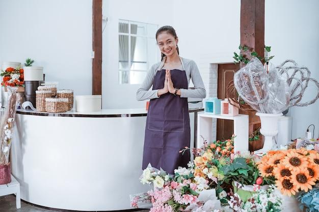 Junger weiblicher florist, der schürze steht, die im front office lächelnd die kamera betrachtet