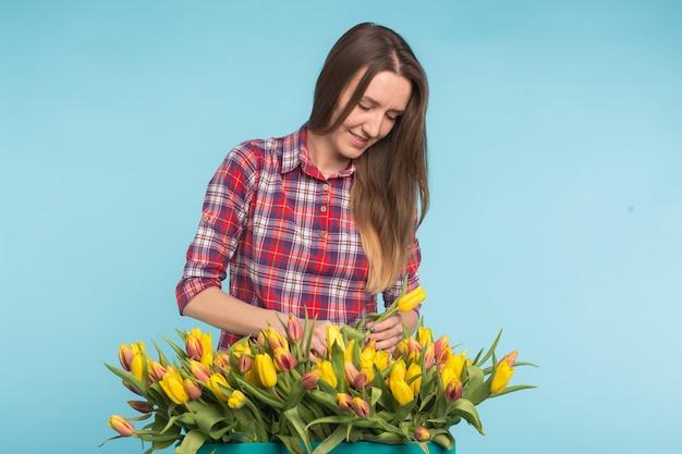 Junger weiblicher florist mit großer schachtel der gelben tulpen auf blauer oberfläche