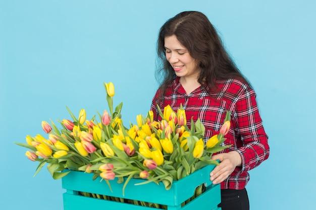 Junger weiblicher florist mit großer schachtel der gelben tulpen über blauem hintergrund