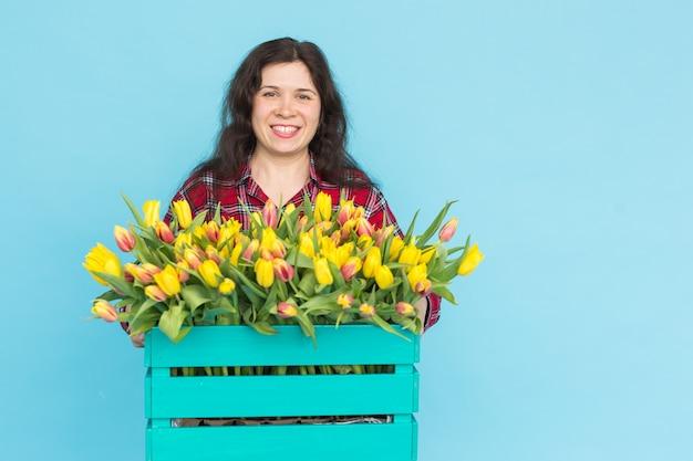 Junger weiblicher florist mit großer schachtel gelber tulpen über blauer wand mit kopienraum