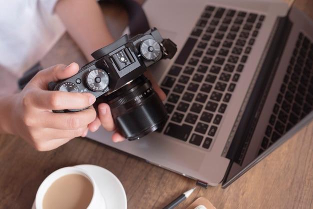 Junger weiblicher fotograf, der bilder auf kameradisplay auf hölzernem schreibtisch überprüft