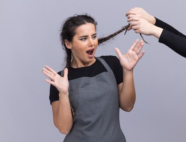 Junger weiblicher friseur in der uniform jemand, der ihr haar isoliert auf weißer wand schneidet
