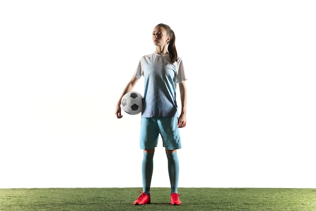 Junger weiblicher fußball- oder fußballspieler mit langen haaren in sportbekleidung und stiefeln, die mit dem ball lokalisiert auf weißem hintergrund stehen. konzept des gesunden lebensstils, des profisports, des hobbys.