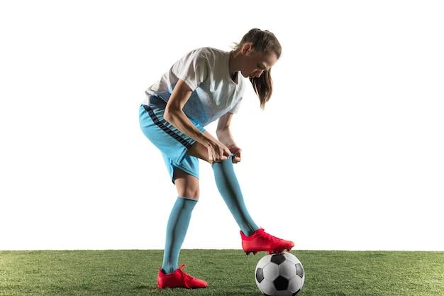 Junger weiblicher fußball- oder fußballspieler mit langen haaren in sportbekleidung und stiefeln, die sich auf das spiel vorbereiten, lokalisiert auf weißem hintergrund. konzept des gesunden lebensstils, des profisports, des hobbys.