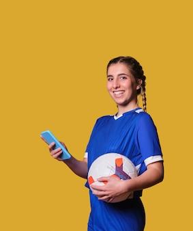 Junger weiblicher fußballfan, der auf sport mit ihrem smartphone setzt