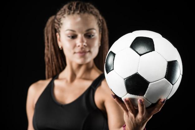 Junger weiblicher fußballspieler, der den ball steht und hält