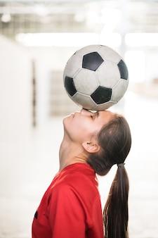 Junger weiblicher fußballspieler im roten t-shirt, das fußball auf ihrer stirn und nase während des trainings im fitnessstudio hält