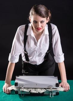 Junger weiblicher gangster auf der grünen tabelle eine tasche des bargeldes.