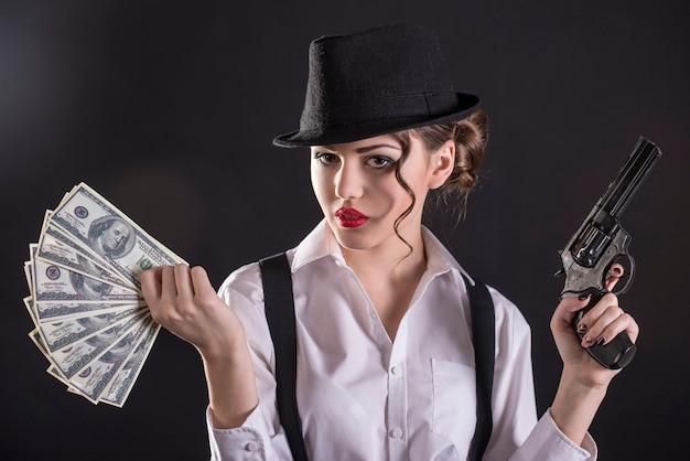 Junger weiblicher gangster, der das gewehr hält und geld zählt.