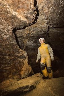 Junger weiblicher höhlenforscher, der die höhle erforscht