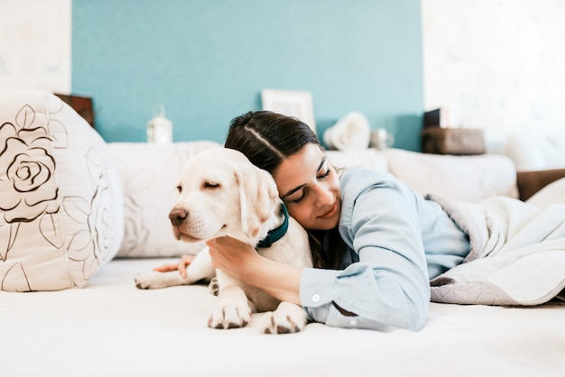 Junger weiblicher inhaber, der im bett mit labrador-welpen schläft.