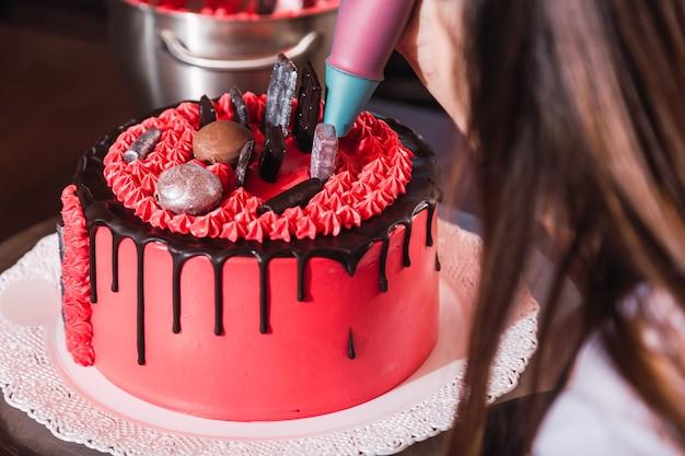 Junger weiblicher konditor, der einen bunten kuchen mit schokolade verziert