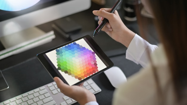 Junger weiblicher kreativer künstler des webdesigns mit dem arbeiten an farbauswahl auf grafischer tablette.