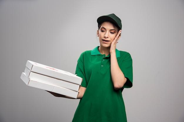 Junger weiblicher kurier, der mit pizzaschachteln aufwirft und ihr ohr bedeckt.