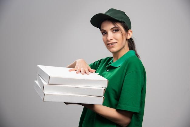 Junger weiblicher kurier, der mit pizzaschachteln aufwirft