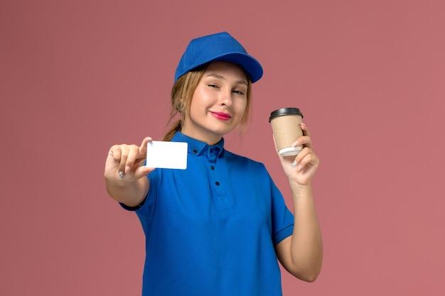 Junger weiblicher kurier der vorderansicht in der blauen uniform, die die tasse kaffee und die weiße karte mit dem lächeln aufstellt, dienstuniformzustellungsfrauenjobarbeiter