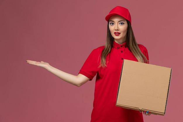 Junger weiblicher kurier der vorderansicht in der roten uniform, die lieferung food box auf hellrosa hintergrund service delivery uniform firma hält