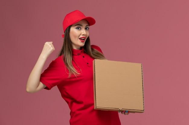 Junger weiblicher kurier der vorderansicht in der roten uniform, die lieferung food box hält, die auf der rosa hintergrunddienstlieferungsuniformfirma jubelt