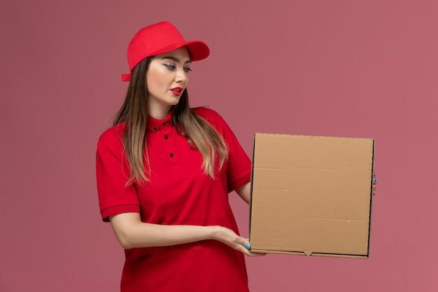 Junger weiblicher kurier der vorderansicht in der roten uniform, die lieferung food box hält, die mit ihm auf der rosa hintergrunddienstlieferungsuniformfirma aufwirft