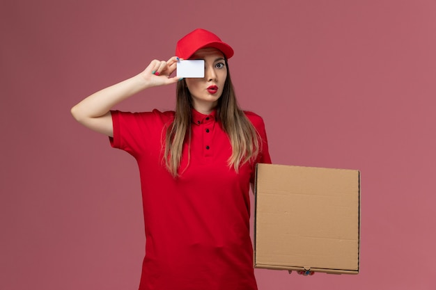 Junger weiblicher kurier der vorderansicht in der roten uniform, die lieferung food box und weiße karte auf hellrosa hintergrund lieferservice uniform firma job hält