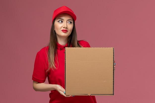 Junger weiblicher kurier der vorderansicht in der roten uniform, die lieferung-nahrungsmittelbox auf der rosa schreibtischdienstlieferuniformfirma hält